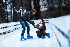 Sirva a la mujer de ayuda para alzarse en pista de patinaje Imágenes de archivo libres de regalías