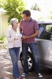 Sirva a la mujer mayor de ayuda en el coche Foto de archivo libre de regalías