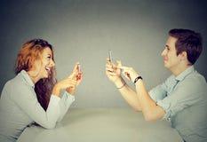 Sirva a la mujer que usa los teléfonos móviles que mandan un SMS tomando imágenes Fotos de archivo libres de regalías
