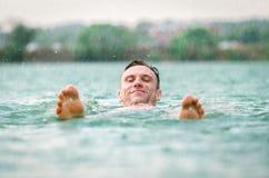 Sirva la natación en el lago debajo de la lluvia en tempestad de truenos fotos de archivo
