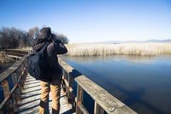 Sirva la naturaleza de observación con los prismáticos, en un puente de madera Imagen de archivo libre de regalías