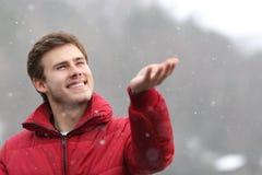 Sirva la observación de la nieve el caer en su mano en invierno Imagenes de archivo