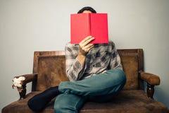 Sirva la ocultación de su cara detrás del libro en el sofá viejo Fotografía de archivo libre de regalías