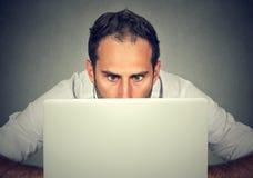 Sirva la ocultación detrás de un ordenador portátil que mira fijamente la pantalla con una expresión chocada de la cara foto de archivo libre de regalías