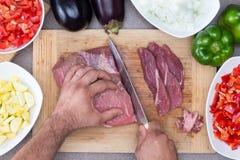 Sirva la preparación de la carne y de verduras en una cocina Imagen de archivo