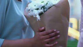 Sirva la presentación del manojo hermoso de camomiles a la señora joven, regalo floral agradable almacen de video