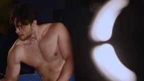 Sirva la presentación en un fondo negro, demostraciones sus músculos Culturista muscular del hombre Sirva la presentación en un f metrajes