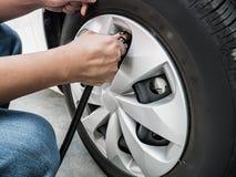 Sirva la presión de aire de relleno en el neumático del coche foto de archivo libre de regalías