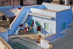 Sirva la reclinación sobre el tejado de un hogar indio tradicional Imágenes de archivo libres de regalías