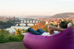Sirva la reclinación en un sofá inflable en la salida del sol Fotos de archivo libres de regalías