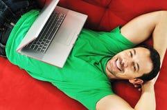 Sirva la relajación en el sofá y trabaje en el ordenador portátil Fotografía de archivo libre de regalías