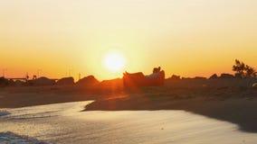 Sirva la relajación en inflable sunbed en la playa en la puesta del sol almacen de metraje de vídeo