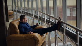 Sirva la relajación en su silla y disfrutar de la visión desde la ventana de la oficina almacen de metraje de vídeo