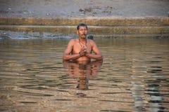 Sirva la rogación dentro de las aguas santas del río Ganga en Varanasi, la India Imagenes de archivo