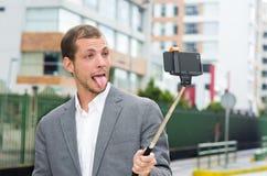 Sirva la ropa formal que presenta con el palillo del selfie adentro Foto de archivo