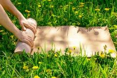 Sirva la rueda de su estera después de una clase de la yoga en un prado verde en un día soleado del verano Foto de archivo libre de regalías