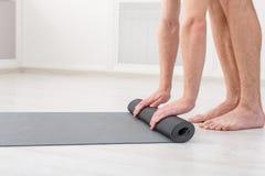 Sirva la rueda de su estera después de una clase de la yoga Imágenes de archivo libres de regalías