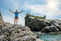 Sirva la situación extendida de los brazos en una roca por el mar Fotos de archivo