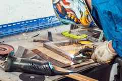 Sirva la soldadura una soldadora del metal en un taller foto de archivo libre de regalías