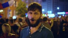 Sirva la sonrisa, después de una victoria del fútbol en ciudad de la noche en la calle en camiseta verde metrajes