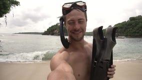 Sirva la sonrisa y la fabricación del selfie con las aletas que llevan una máscara del salto en la playa del océano metrajes