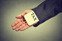 Sirva la tarjeta de ocultación del impuesto de la mano en una manga de un traje concepto de la economía de la evasión fiscal Imagenes de archivo