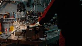 Sirva la tuber?a de acero del corte con una amoladora de ?ngulo produciendo chispas calientes imagen de archivo