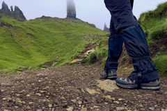 Sirva las botas y las polainas del senderismo que llevan que caminan al viejo hombre de Storr Foto de archivo