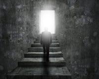 Sirva las escaleras concretas que suben hacia puerta con la luz brillante Imagenes de archivo