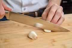 Sirva las manos del ` s que cortan el ajo fresco en la cocina, preparando una comida para el almuerzo imagen de archivo libre de regalías