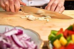 Sirva las manos del ` s que cortan el ajo fresco en la cocina, preparando una comida para el almuerzo Paprika y cebollas en el pr foto de archivo