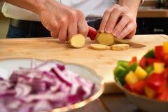 Sirva las manos del ` s que cortan los tomates frescos en la cocina, preparando una comida para el almuerzo Visión de arriba haci fotos de archivo