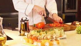 Sirva las manos del ` s que cortan verduras en restauran metrajes