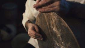 Sirva las manos del ` s que teclean hacia fuera un golpe en un tambor árabe de la percusión nombrado Bendir metrajes