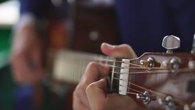 Sirva las manos del ` s que tocan la guitarra acústica, cierre para arriba almacen de video
