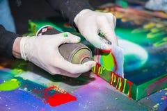 Sirva las manos en los guantes que se sostienen y que dibujan por el espray de la pintada Imagen de archivo