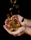 Sirva las manos por completo del dinero que recibe una lluvia de monedas Imagen de archivo