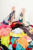 Sirva las manos que alcanzan hacia fuera de una pila grande de ropa y de accesorios Fotografía de archivo libre de regalías