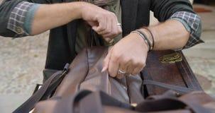 Sirva las manos que buscan en equipaje o la maleta del asiento trasero para los guantes Pares reales caucásicos en italiano de la almacen de metraje de vídeo