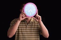 Sirva las manos que llevan a cabo delante de su cara un showin grande del reloj de pared Imágenes de archivo libres de regalías