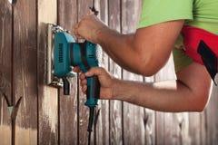 Sirva las manos que pulen la cerca vieja con la herramienta eléctrica Foto de archivo libre de regalías