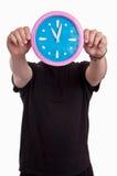 Sirva las manos que sostienen delante de su cara un reloj de pared grande que muestra tiempo Imagen de archivo libre de regalías