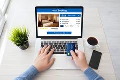 Sirva las manos que sostienen el ordenador portátil de la tarjeta de crédito con la reservación de hotel del app fotos de archivo libres de regalías