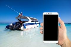 Sirva las manos que sostienen el teléfono elegante con el barco de la velocidad que flota en el mar Imagen de archivo libre de regalías