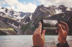 sirva las manos que sostienen el teléfono móvil en el mar y las montañas Fotos de archivo