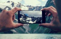 sirva las manos que sostienen el teléfono móvil en el mar y las montañas Imagen de archivo libre de regalías