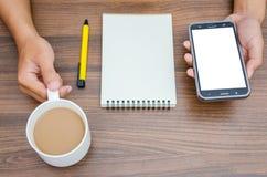 Sirva las manos que sostienen el teléfono y que sostienen una taza de café caliente con el espacio en blanco Fotografía de archivo libre de regalías