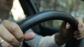 Sirva las manos que sostienen el volante mientras que conduce el coche metrajes