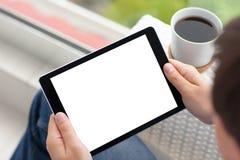 Sirva las manos que sostienen la tableta con la pantalla y el coffe aislados Foto de archivo