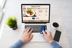 Sirva las manos que sostienen la tarjeta de crédito y el ordenador portátil con entrega de la comida Imágenes de archivo libres de regalías